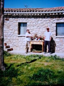 Liz Crain and Anders stand in front of a white stone Spanish farm house in 1996