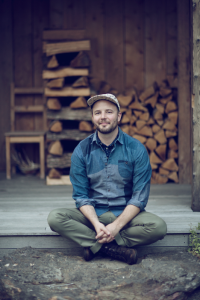 Joshua McFadden, sitting at a cabin on the stoop in front of a pile of logs